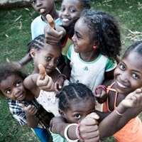 Glada barn som gör tummen upp. Foto: Giorgio Minguzzi.
