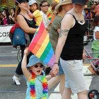 En liten flicka med regnbågsflagga.