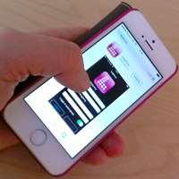 Hand som håller en smattelefon med appen Legimus.
