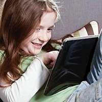 Flicka läser på en surfplatta