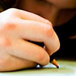 Flicka som skriver med penna.