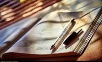 Uppslagen bok med penna på.