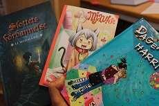 En hand som håller upp tre barnböcker
