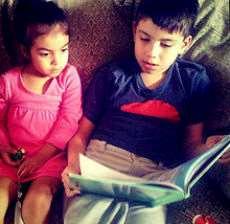 En pojke och en flicka sitter i soffan och läser en bok tillsammans