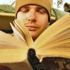 Ung man som läser en bok.