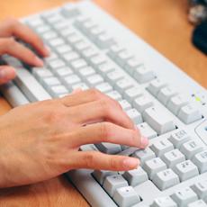 Två händer på ett tangentbord till en dator.