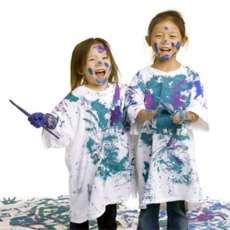 Två små flickor med penslar och målarfärg på sina tröjor.
