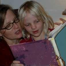 En mamma läser högt för sin dotter.