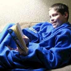 Pojke under filt läser en bok i soffan