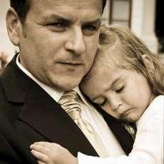Pappa med barn i famnen.