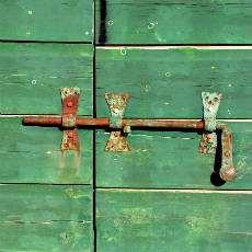 Detalj av en gammal grön dörr med lås.