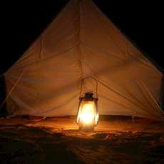 En fotogenlykta framför ett tält.