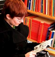 Läsande kvinna vid bokhylla.
