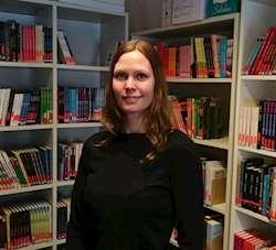Skolbibliotekarie Erika Käll framför bokhyllor