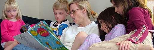 Vuxen som läser för flera barn. Foto: Ned Horton, stock.xchng