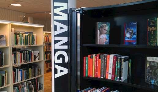 Interiör från Knivsta bibliotek med den svarta bokhyllan för ungdomsböcker och manga.