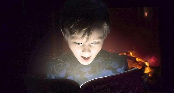 Hänförd pojke läser uppslagen bok som det strömmar ljus ur.