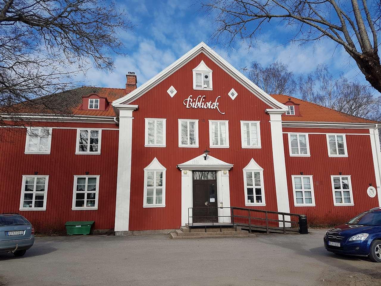 Röd och stor träbyggnad med biblioteksskylt