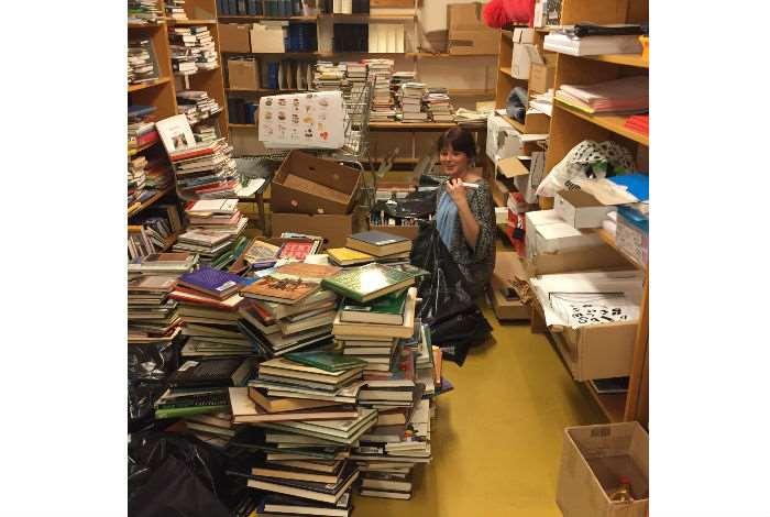 Kvinna omgiven av travar med böcker