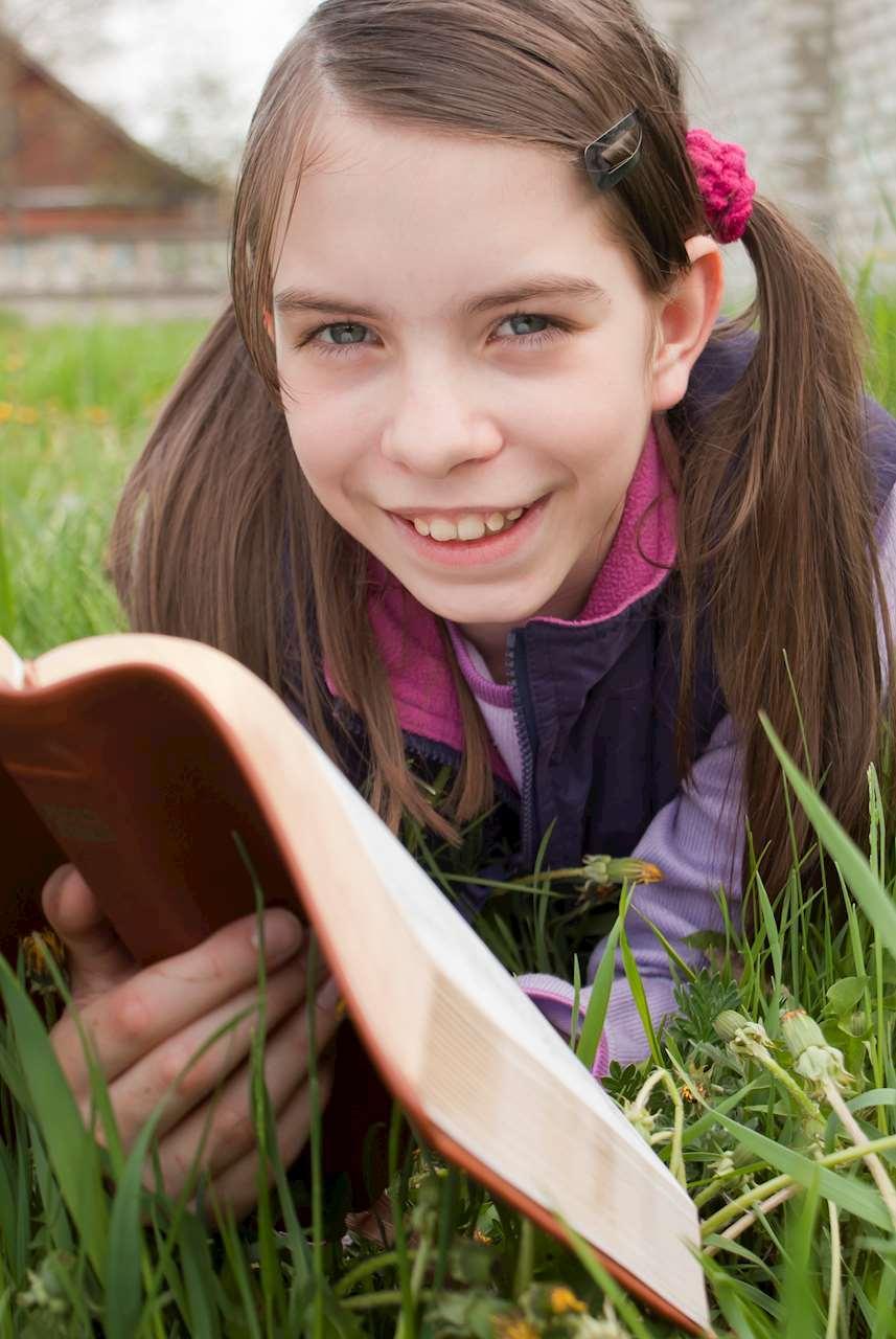 Läsande barn i gräs