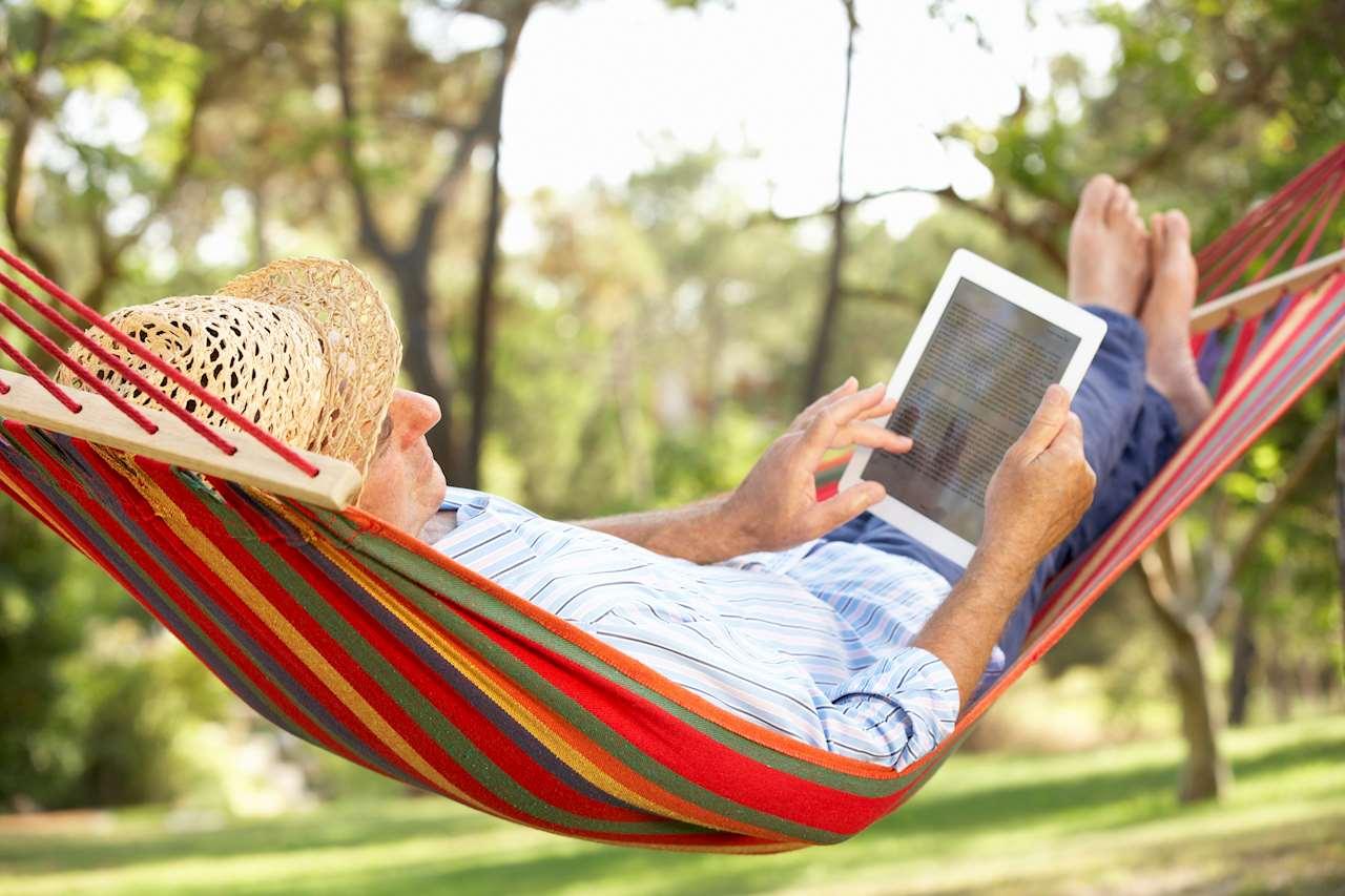 Man i hängmatta läser e-bok