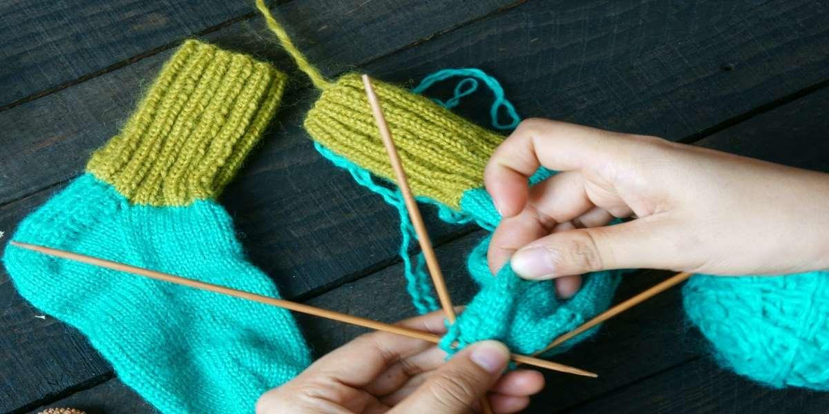 Strumpor i två färger, stickor och händer