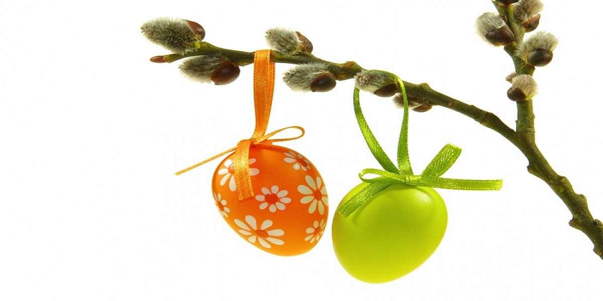Två målade ägg hänger på en gren med knoppar på.